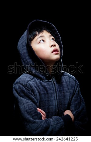 Cute Asian boy wearing hooded sweatshirt posing in studio. Isolated on black. - stock photo