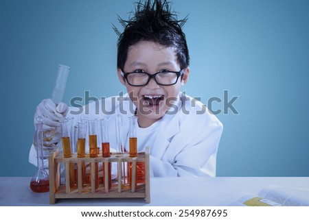 Cute asian boy wearing lab coat doing experiment like a mad scientist - stock photo