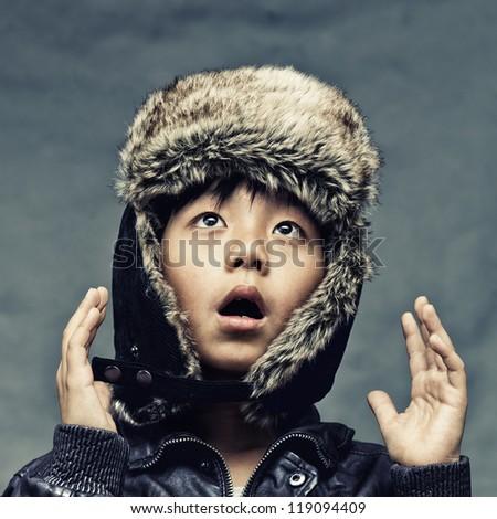 Cute Asian boy wearing winter hat looking surprised - stock photo