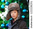 Cute Asian boy with winter hat in front of decorated Christmas tree - stock photo