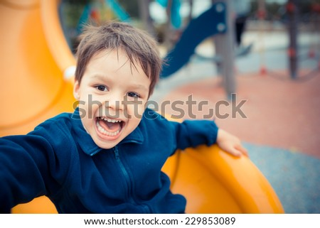 Cute Asian Caucasian mixed race toddler happily playing on a slide in a playground outside in the summer sun - stock photo