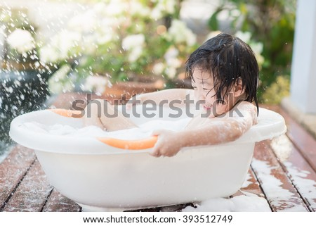 Cute asian  child bathing in the garden - stock photo