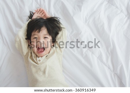 Cute asian child lying on white bed - stock photo