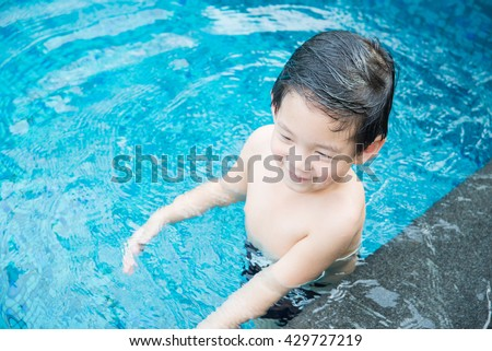 Cute Asian child playing in swimming pool