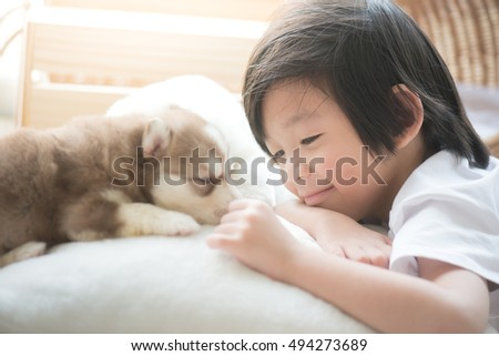 Cute asian child playing with siberian husky puppy