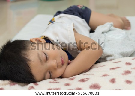 Cute asian child sleep on Sleeping pad.