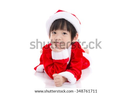 Cute asian child wearing Santa Claus uniform lying on white background isolated