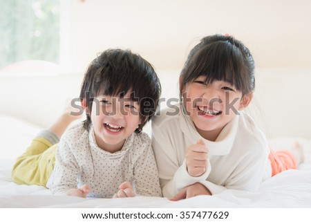 Cute asian children lying on white bed,vintage filter - stock photo