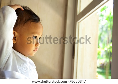 cute asian ethnic little girl dressed in white look out the window - stock photo
