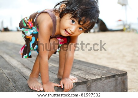 Cute asian ethnic little girl having fun at the beach - stock photo