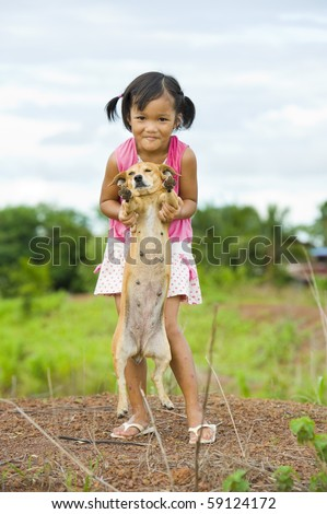 cute asian farmer girl holding a young dog - stock photo