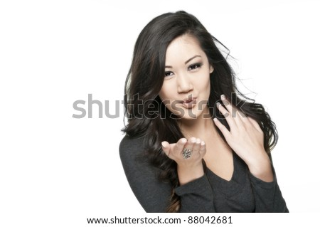 cute asian girl blowing a kiss, white background - stock photo