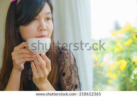 Cute asian girl drinking hot coffee. - stock photo