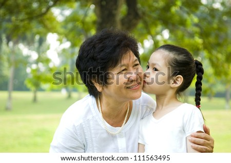 cute asian girl giving a kiss to grandmother - stock photo