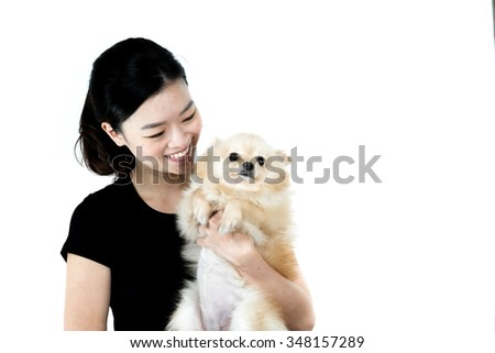 Cute asian girl holding Pomeranian dog, isolated on white background