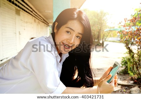 cute Asian girl holding smart phone, technology concept background  - stock photo