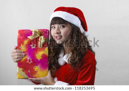 cute asian girl in santa claus clothes holding gift