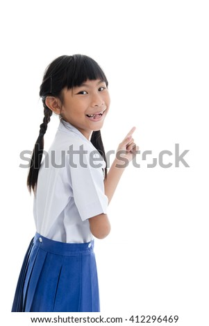 Cute Asian girl in uniform showing her broken teeth on white background.