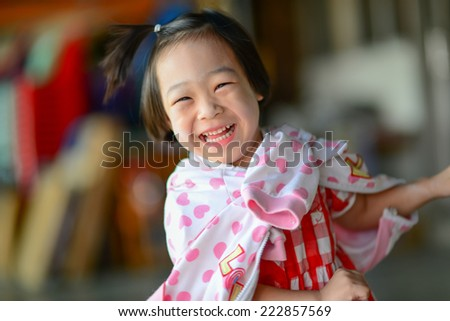 Cute Asian girl laughing. - stock photo