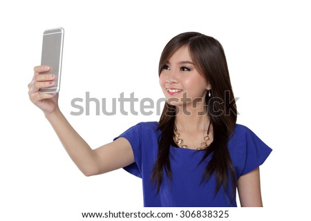 Cute Asian girl look at her smartphone, take a selfie and smiles, isolated on white background - stock photo