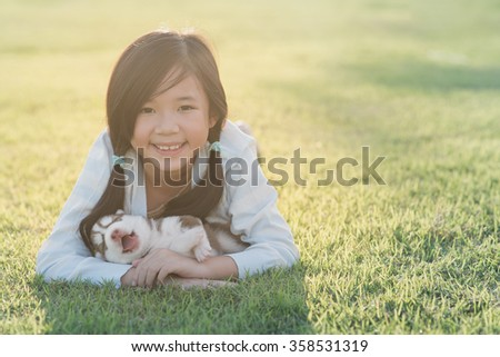 Cute asian girl lying with her puppy on green grass - stock photo
