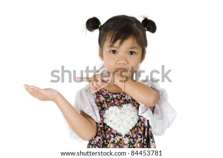 cute Asian girl pointing at something in her hand, isolated on white background - stock photo
