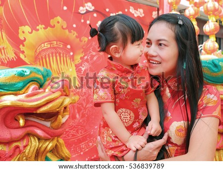 Cute Asian Girl smile and hug her child In Tradition Chinese dress at Chinese new year.