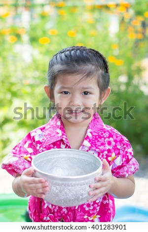 Cute Asian girl smiling  and holding water cup for Songkran festival Thailand.Songkran ceremony, Thai New Year. - stock photo