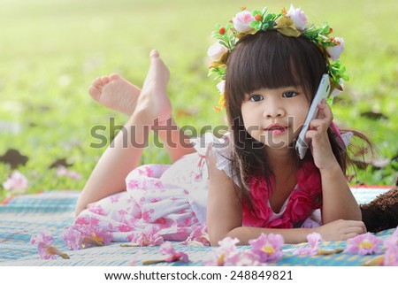 Cute Asian girl smiling and talking on her cell phone in the park - stock photo