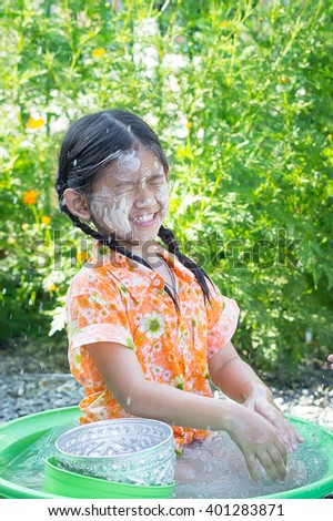 Cute Asian girl smiling when she playing water in her little plastic basin on Songkran fastival Thailand.Songkran ceremony, Thai New Year. - stock photo