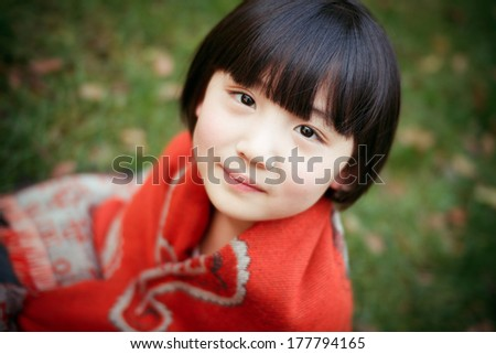 Cute asian girl, standing on the grass - stock photo