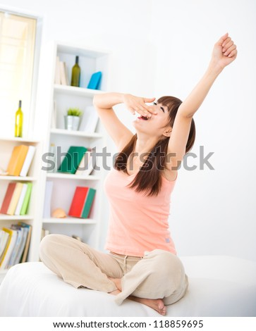 Cute Asian girl waking up on bed and yawning - stock photo