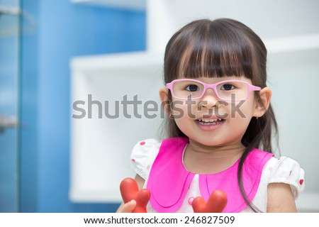 Cute Asian girl wearing glasses. playing toys happily. - stock photo