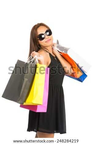 Cute Asian girl with department store shopping bags over both shoulders wearing black dress, oversized sunglasses, head tilted smiling at camera. Half Length Isolated. Thai national of Chinese origin - stock photo