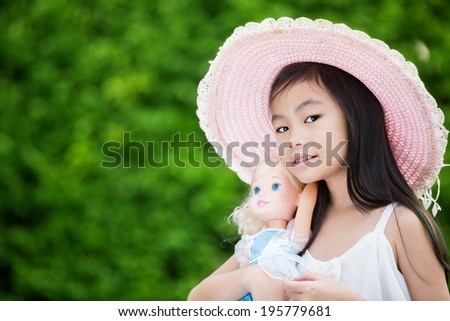 Cute Asian girl with doll - stock photo