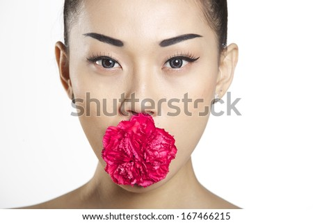 Cute asian girl with red carnation in mouth - stock photo