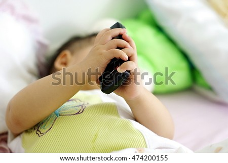 Cute Asian infant baby in white dress is lying and holding phone on her bed.