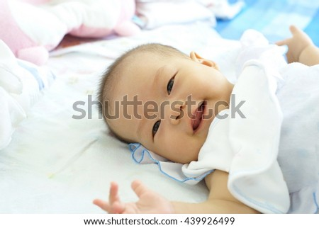 Cute Asian infant baby in white dress is lying and smiling on her bed. - stock photo