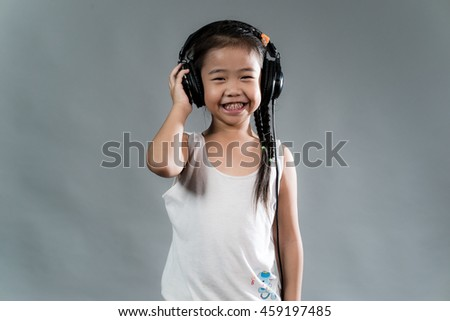 Cute Asian kid girl enjoying music using headphones - stock photo