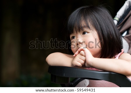 Cute Asian little girl smiling and with both hands holding together - stock photo