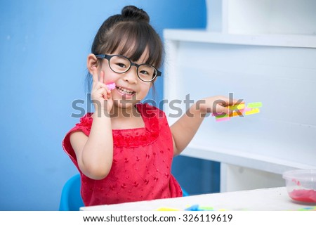 Cute Asian little girl  Wearing a red shirt and glasses playing toys happily. - stock photo