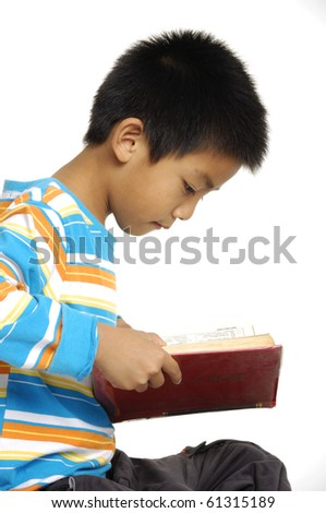 Cute asian schoolboy sitting reading book isolated - stock photo