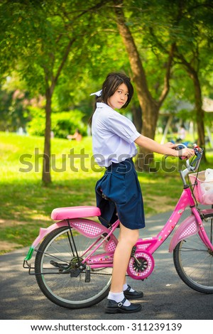 Cute Asian Thai schoolgirl student in high school uniform fashion is standing over her pink bicycle ready to exercise in sunny summer park with green environment - stock photo