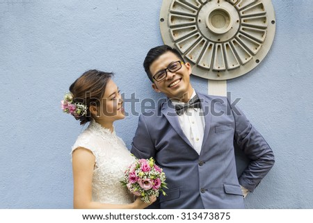 Cute Asian wedding photo shooting with antique blue color wall background - stock photo