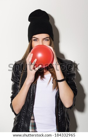 Cute attractive Caucasian teenage hipster girl blowing a red balloon wearing leather jacket and beanie hat. - stock photo