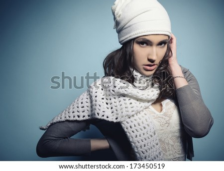 Cute attractive fashion young girl in warm clothes, over blue, toned - stock photo