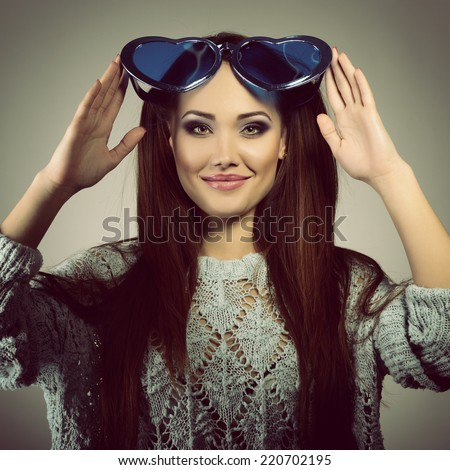 Cute attractive fashion young girl posing with funny big love blue heart glasses, image toned.