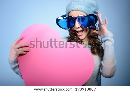 Cute attractive fashion young girl posing with funny big love glasses and pink heart, over blue background