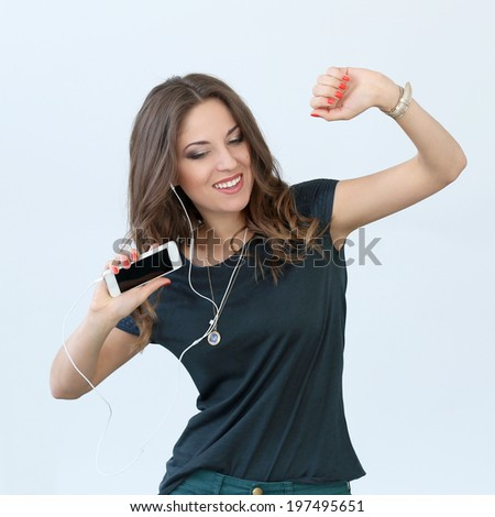 Cute, attractive girl with mobile phone and headphones - stock photo