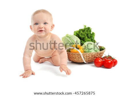 Cute baby and fresh vegetables in wicker basket on white background - stock photo